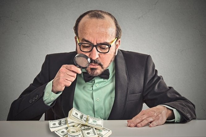 penny pincher. Business man looking through magnifying glass on stack of dollar banknotes on table isolated grey office background. Economy financial wealth success concept. Ponzi scheme investigation